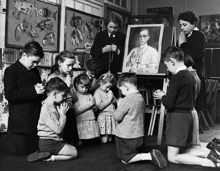 Leerlingen van een Italiaanse school bidden bij een portret van Paus Pius XII nadat die was getroffen door een hartaanval in oktober 1958. Beeld Corbis via Getty Images