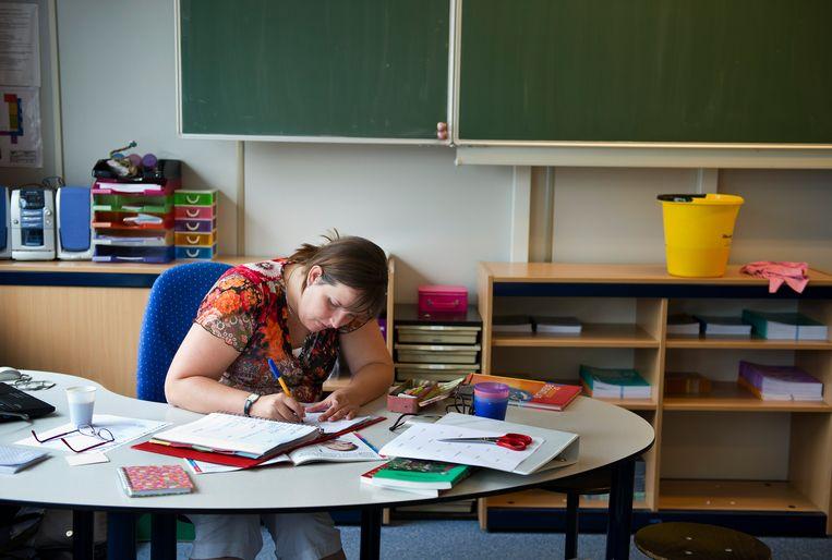 Een leerkracht kijkt huiswerk na.  Beeld ANP XTRA, Robert Vos