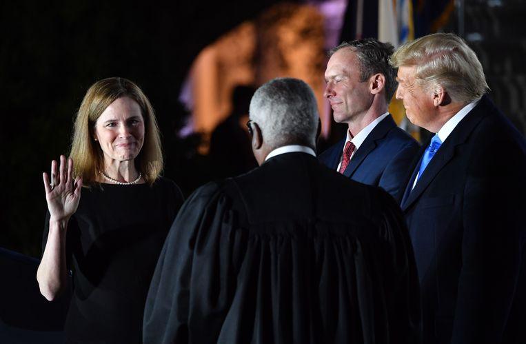 Amy Coney Barrett (l) legt de eed af voor Clarence Thomas (midden), die rechter aan het Hooggerechtshof is. Beeld AFP
