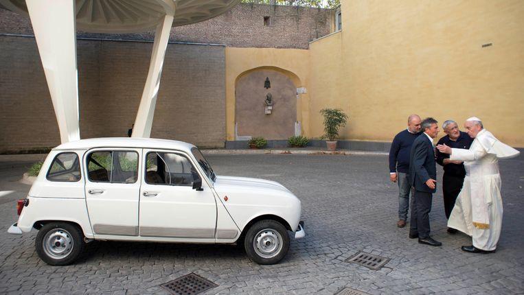 De Renault 4L van paus Franciscus. Rechts de gelukkige nieuwe eigenaar, in gesprek met de gulle gever, priester Renzo Zucca. Links autoreperateur Stefano. Beeld AP