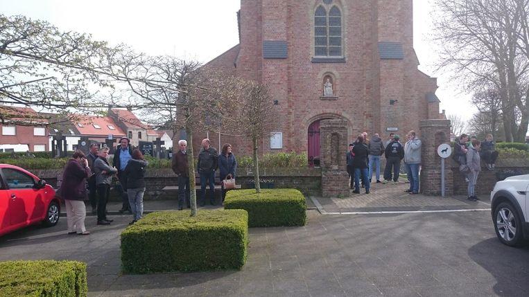 Enkele bewoners van Sint-Pieters-Kapelle wachten aan de kerk op de brandweer voor ze hun huizen opnieuw mogen betreden.