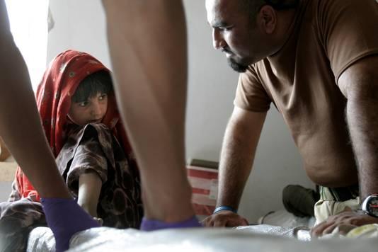 Een Afghaans meisje met een tolk in het Nederlandse kamp Deh Rawood in 2006.