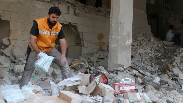 Een hulpverlener doorzoekt het puin van een medisch depot na een luchtaanval op Aleppo op 30 april 2016.
