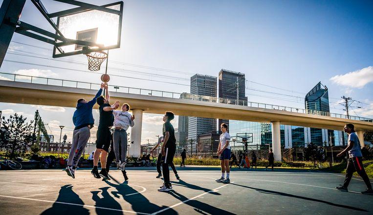 Jongeren spelen zaterdag basketbal op een veldje in Den Haag.  Beeld Freek van den Bergh / de Volkskrant