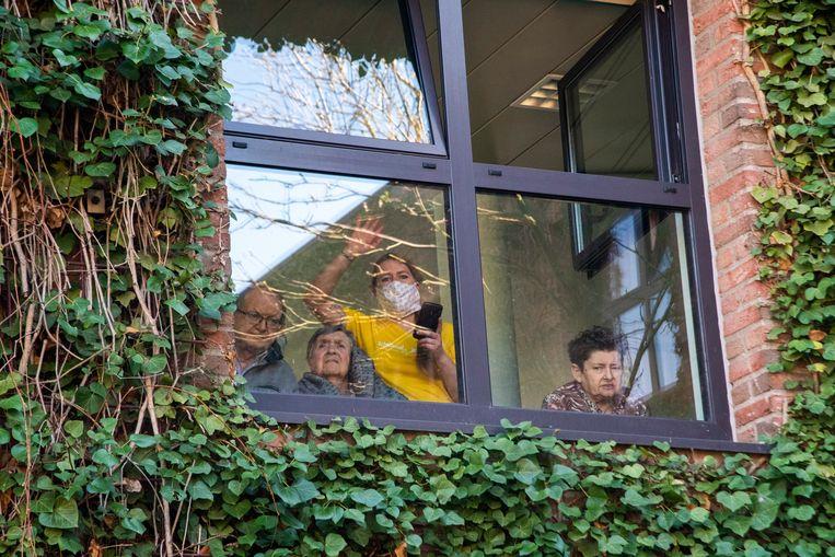 Bewoners genieten vanachter het glas van het optreden aan WZC Schelderust.
