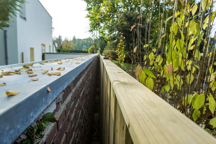 De bewuste muur van burgemeester Blanksma (links) en de houten schutting die de familie Reinders noodgedwongen tegenaan zette.