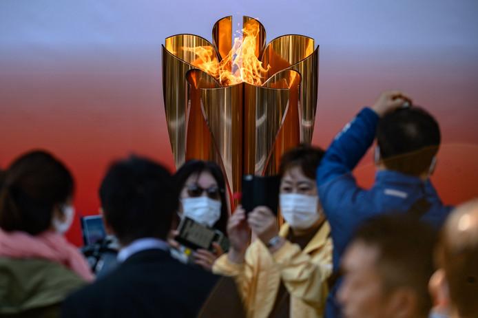 In Tokio maken mensen met mondkapjes foto's van de olympische vlam.