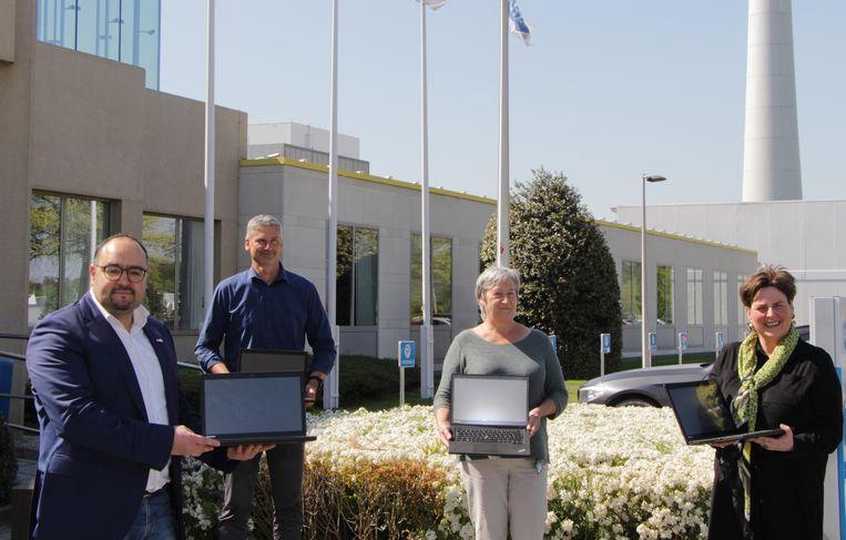 Schepen Abdel El-Hajoutti (CD&V), links, en schepen Inge De Ridder (N-VA), uiterst rechts, nemen de laptops in ontvangst.