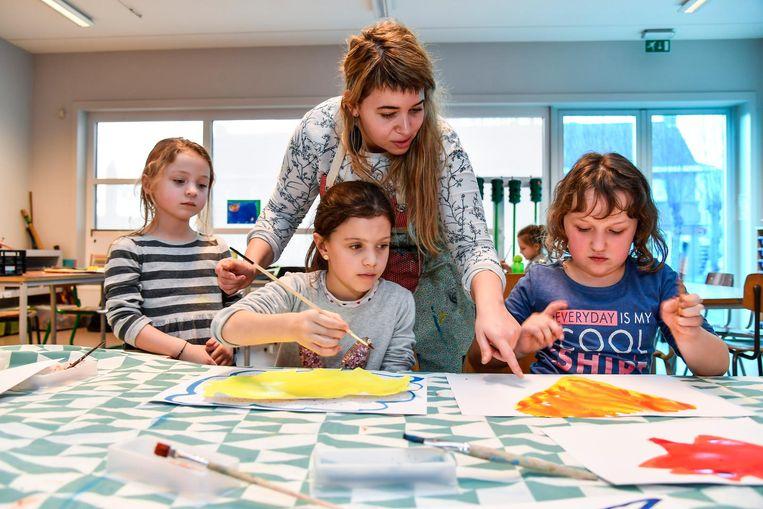 Een leerkracht van de Academie helpt de kinderen bij het schilderen.