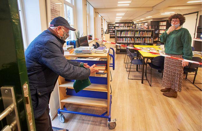 Theo Schultz schuift zijn gelezen boeken in een kar, terwijl Els Mutsaers zijn verse leesvoer achter op een tafel klaar heeft liggen.