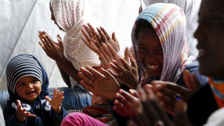 Een baby uit Ethiopië zit tussen Eritrese en Ethiopische vluchtelingen in Calais.