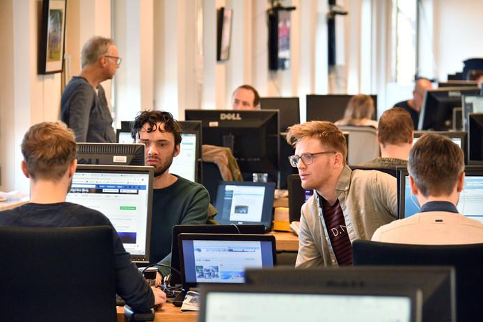 Verslaggevers Arjen ten Cate (l) en Stefan Keukenkamp overleggen over een verhaal dat ze aan het maken zijn op de redactie van de Stentor. Op de achtergrond vertelt Vechtdal-verslaggever Benny Koerhuis aan zijn leidinggevende Arjan Bosch over een artikel waaraan hij werkt.