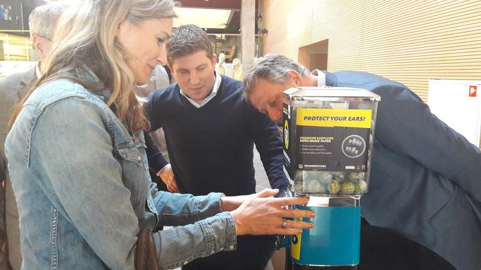 Communicatie-adviseur Vivian Jansen probeert de Bladelse oordoppenmachine aan de praat te krijgen. In het midden staat wethouder Davy Jansen en rechts burgemeester Bosma.