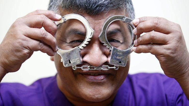 De bekende Maleisische politiek tekenaar Zulkiflee Anwar Alhaque, alias Zunar, vanochtend bij het verlaten van de rechtbank. Met plastic handboeien maakt hij grappen over de gevangenisstraf die hem mogelijk boven het hoofd hangt. Beeld epa