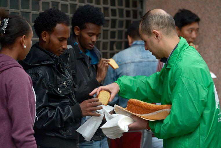 Vakbondsleden verwelkomden de lange rij asielzoekers met flesjes water en cake.