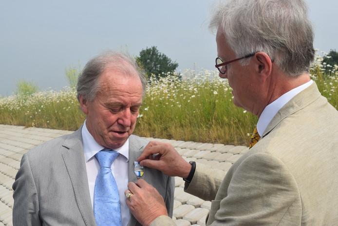 Heemraad Leo van Gelder de onderscheiding opgespeld door Peter Glas.