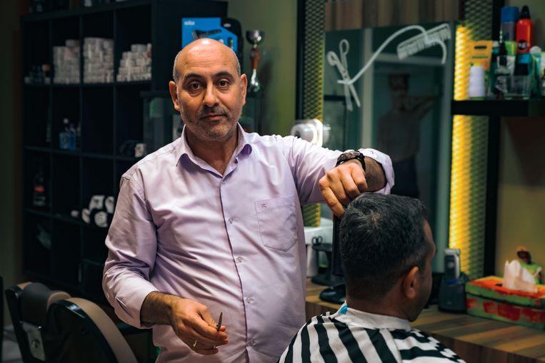 Hussain, ooit een vluchteling, nu eigenaar van een kapperszaak.