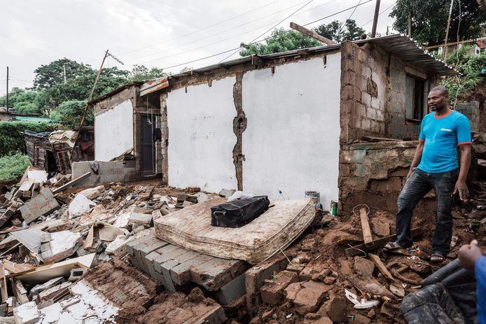 Jason Mthembu staat naast de resten van zijn huis dat door de overstromingen en hevige regenval vernietigt werd.