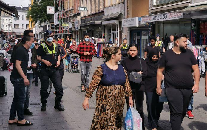 De politie spreekt winkelende mensen aan en verplicht hen de andere richting uit te stappen.
