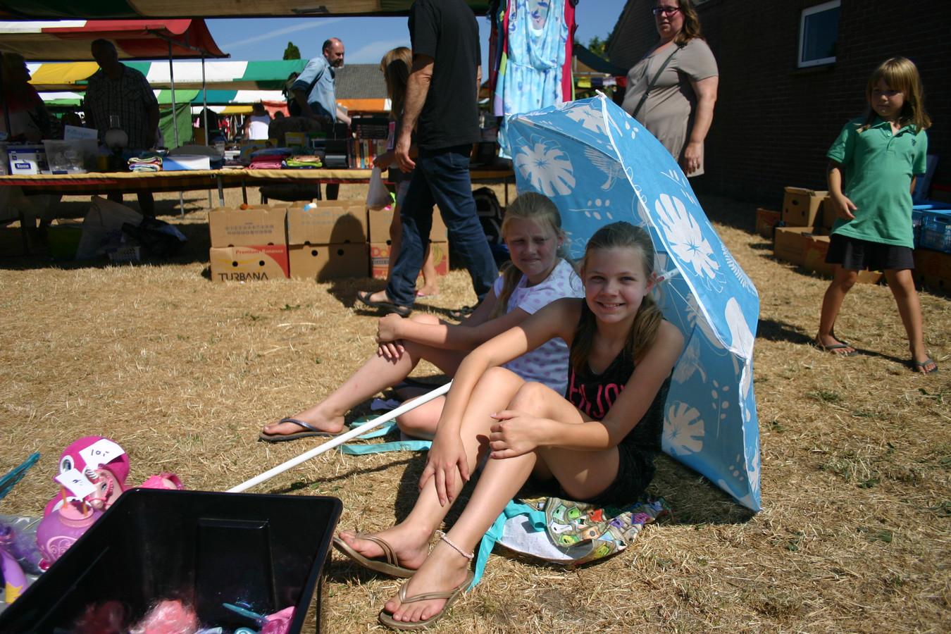 Onder hun parasol zitten Faith (links) en Summa van negen jaar bij hun roze spulletjes op de jaarmarkt van Baarschot