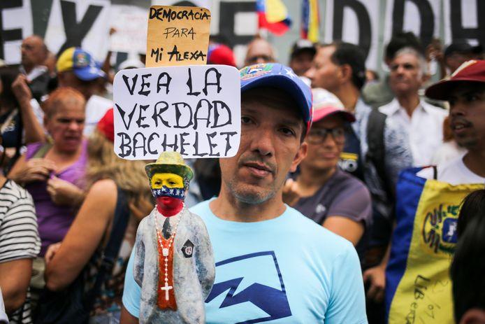 """Een aanhanger van de oppositie betoogt buiten het hoofdkwartier van het ontwikkelingsprogramma van de VN met een bord met de tekst """"Zie de waarheid Bachelet""""."""