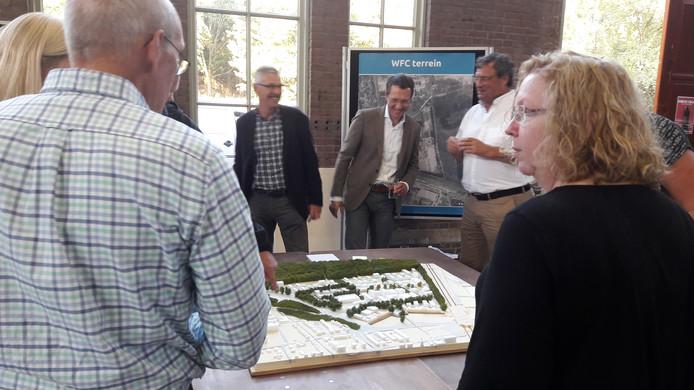 Bezoekers buigen zich over de maquette van het World Food Center.