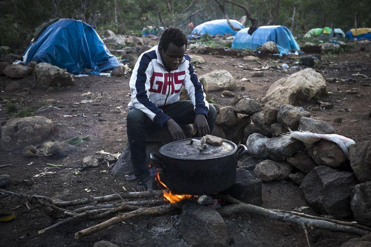 Een man uit Guinee bereidt zijn avondmaal in een Marokkaans migrantenkamp Beeld AP