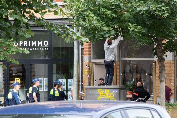 Een politieman demonteert een bewakingscamera op het terras van het getroffen pannenkoekenhuis.