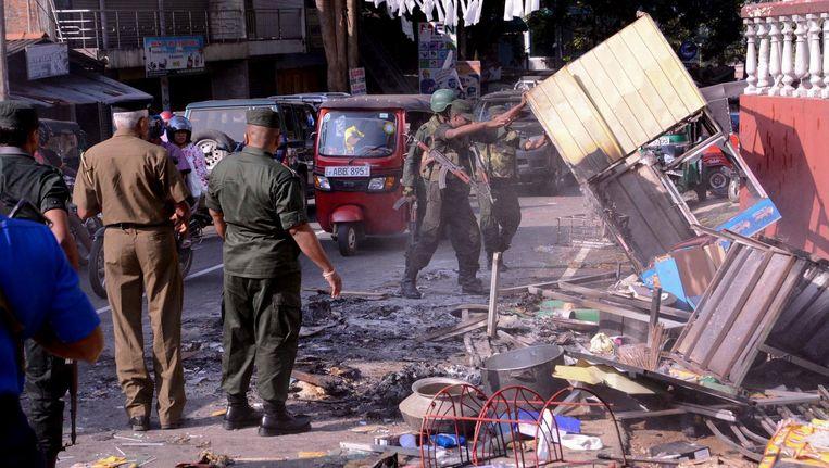 Soldaten verwijderen puin op straat in Digana, een buitenwijk van Kandy, waar eerder maandag een Singalese menigten door moslimwijken trok en zo'n dertig woningen en winkels vernielde. Beeld null