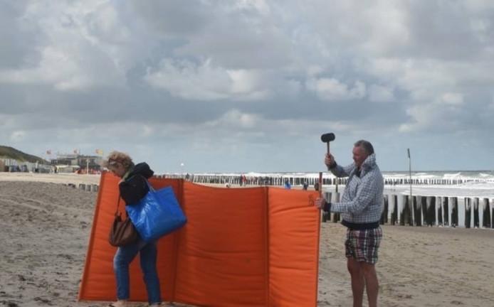 Een windscherm opzetten op het strand.