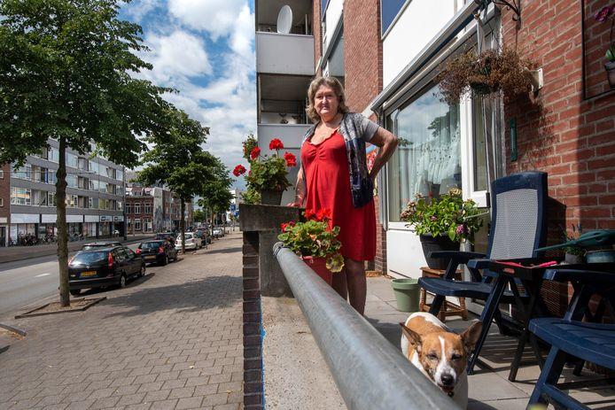"""Hanny Hessing met hondje Djeny op haar balkon aan de Van Muijlwijkstraat in Arnhem. ,,Hier is altijd wat te zien."""""""