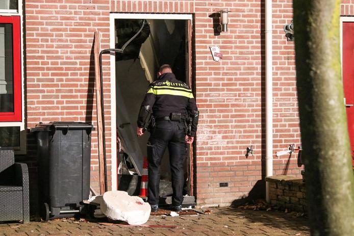 Agenten inspecteren de woning waar de voordeur van verdwenen is.