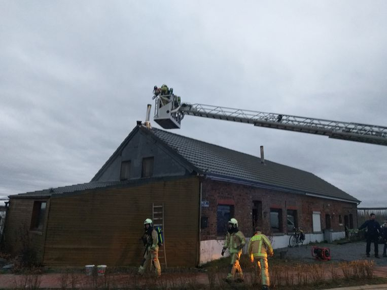 De brandweer blust de dakbrand.