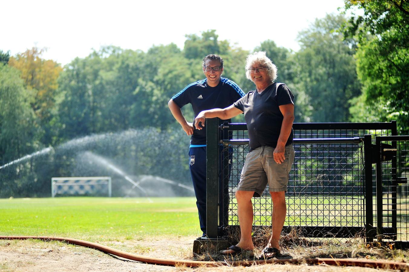 Oury Shem-Tov van Fletcher Hotels (links) en Richard Vacquier Droop, voorzitter van Duno, besproeiden het veld tijdens de droogte met een tuinslang.