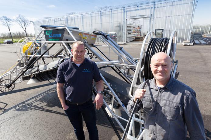 Marcel Koolmees (l) en Joost van der Waay staan bij hun reininigingsmachine voor kassen.