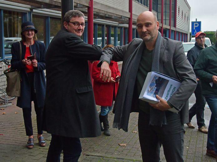 SP-Kamerlid Jasper van Dijk overhandigt het zwartboek met een elleboogje aan Dethon-directeur Edwin van den Berghen.