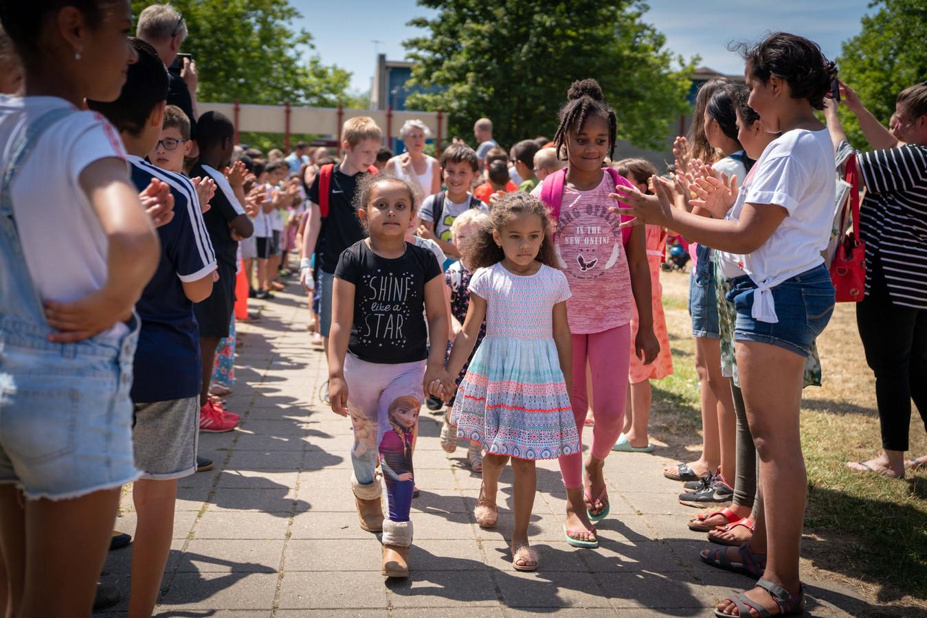 De kinderen van de Dreesschool vormen een erehaag voor de kinderen van de Kennedyschool, met wie ze vanaf komend schooljaar samen de nieuwe Parkschool zullen vormen.