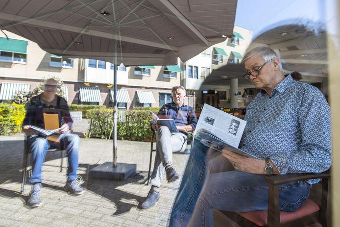 Jan Meijer (rechts) bladert binnen in De Meergaarden door het jubileumboek van FC Eibergen. Buiten zitten Johan Schot (links) Wilfried Schilderinck  van de Eibergse voetbalclub.