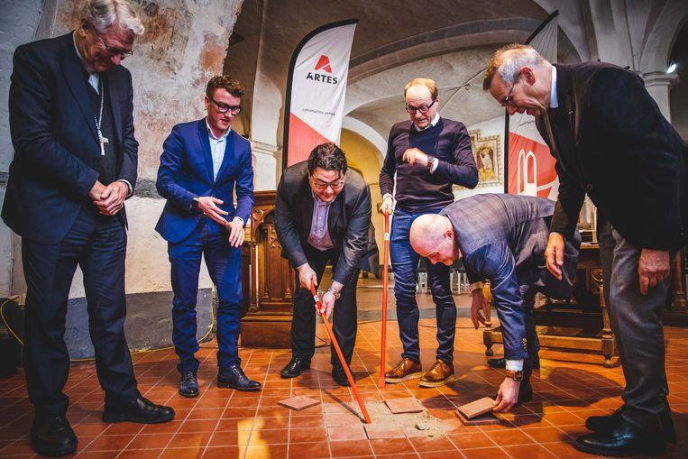 Bisschop Van Looy, schepenen Van Braeckevelt en Souguir, minister Weyts, gedeputeerde Moens en administrateur-generaal van Toerisme Vlaanderen Peter De Wilde breken samen de eerste tegels uit in de crypte van de Sint-Baafskathedraal.