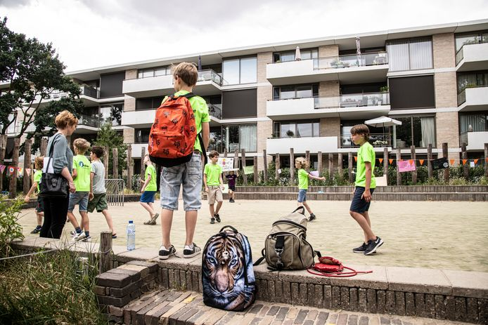 Kinderen verzamelen zich op het gewraakte voetbalveldje achter de school.