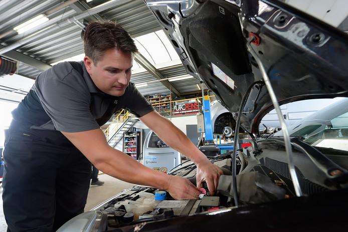 Rens van Belzen van autobedrijf Rens in Roosendaal vult net voor het begin van de vakantie een airco bij.