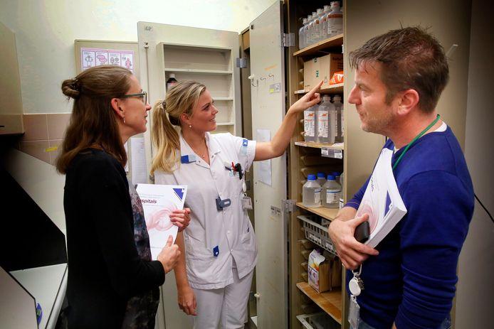 Petran Geurts en Willemijn Fraanje kijken met verpleegkundige Jessica Petter in de medicijnkamer of alles op orde is.