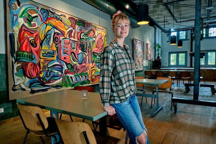 Organisator Leanne van Gurp in de bovenzaal van Merz. Op de achtergrond hangt een schilderij van Gerben Gerrit.