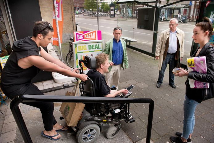 Marcel Brans van de werkgroep Toegankelijke Evenementen wordt geholpen bij het afdalen van een hellingbaan. Tweede van rechts, Wilbert Willems, voorzitter van het platform Breda voor Iedereen.