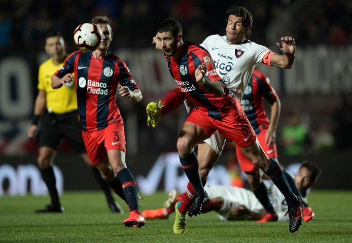Marcos Senesi kopt de bal weg namens zijn club San Lorenzo.