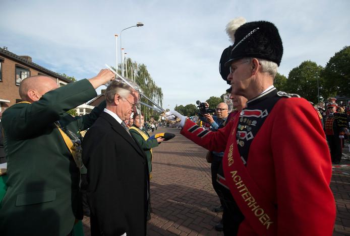 Commissaris vd Koning John Berends krijgt de versierselen omgehangen.