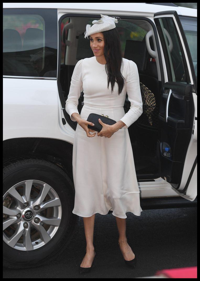 Meghan Markle in een loszittende, lange, witte jurk waarin haar armen bedekt zijn. Ze droeg deze outfit in Fiji.
