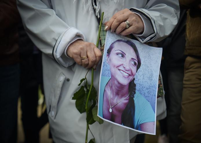 In een mars ter herinnering aan de vermoorde Julie Douib houdt een vrouw een portret van de omgekomen Franse vast.