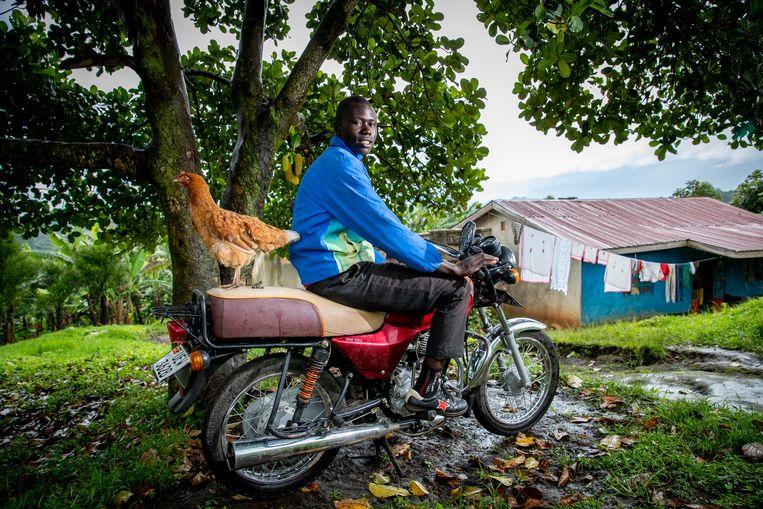 James (19) op zijn bodaboda, een prachtige motortaxi die hij gefinancierd heeft met de opbrengsten van zijn kippenkwekerij.