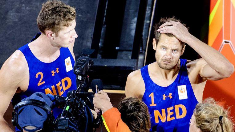 Reinder Nummerdor (R) en Christiaan Varenhorst na hun verlies tegen Alexander Brouwer en Robert Meeuwsen tijdens de kwartfinale beachvolleybal in de Beach Volleybal Arena op de Olympische Spelen in Rio. Beeld ANP